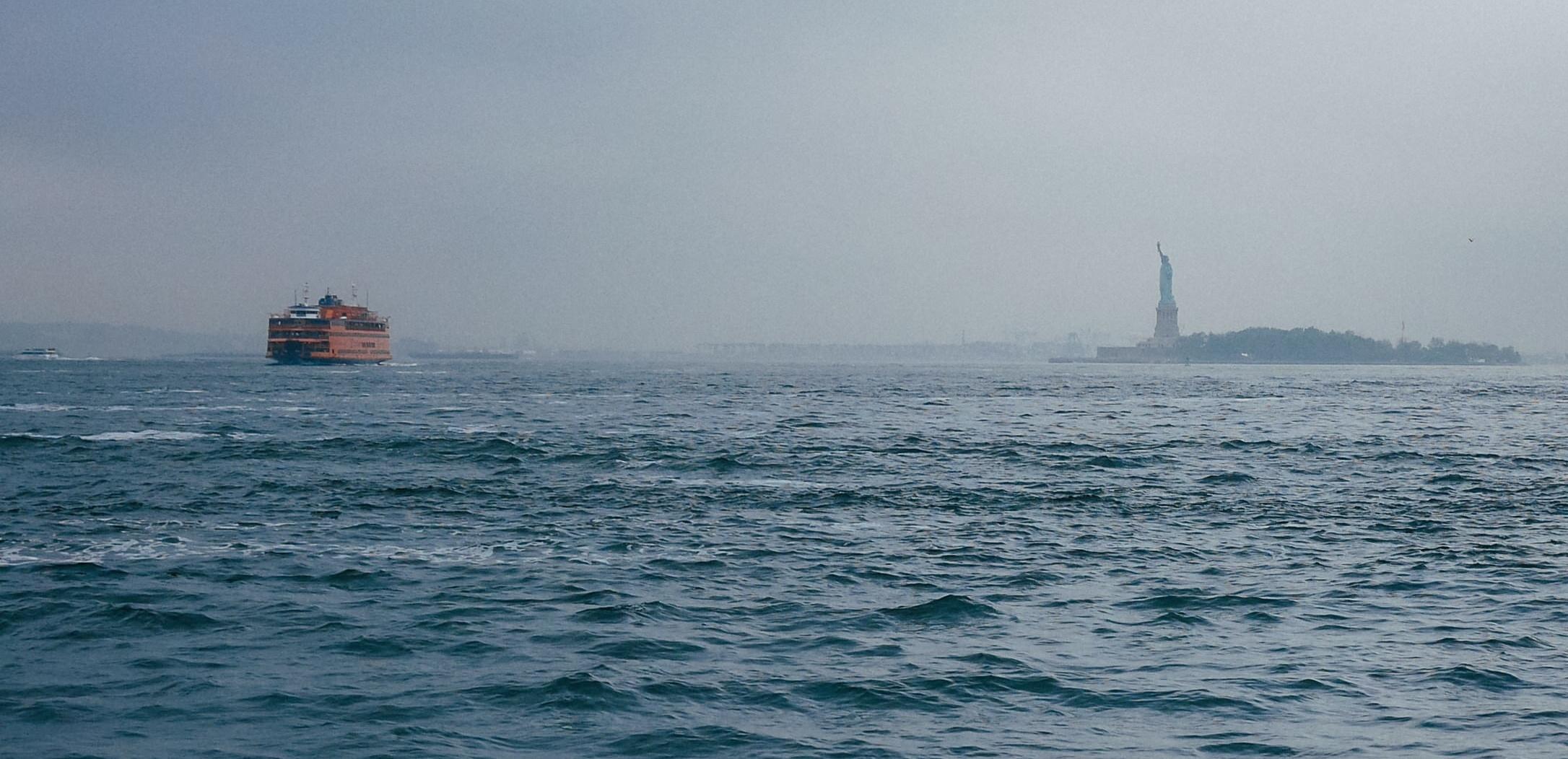 The Statue of Liberty in the distance from the ocean.