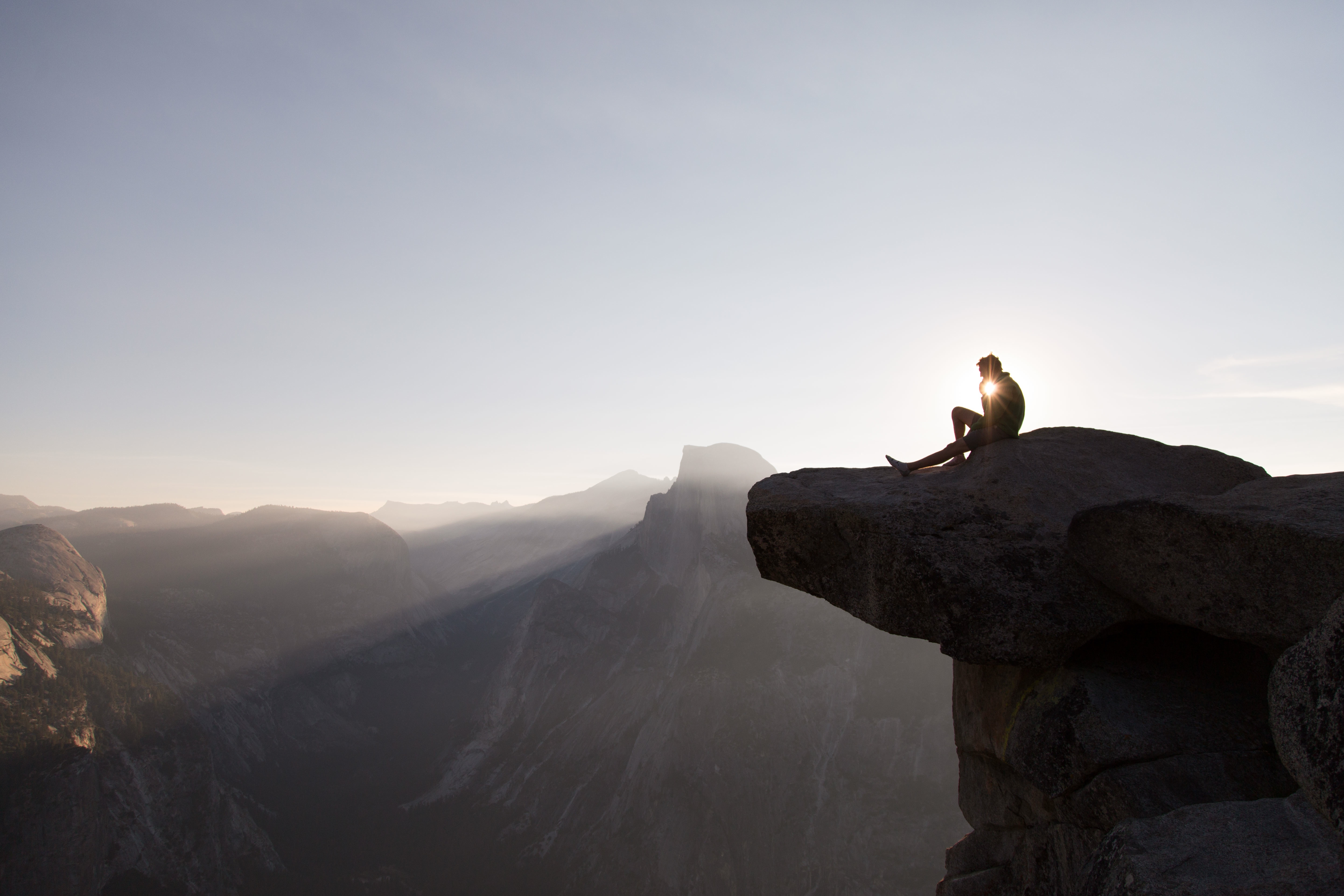 A person sitting on a cliff with sunset behind.