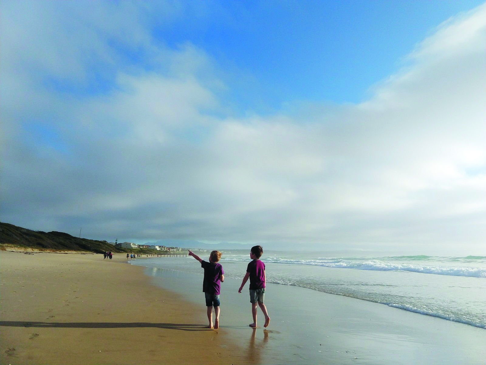 Two young boys walking along a beach, one pointing at something in the distance to the other. Wispy clouds cover part of the bright blue sky!
