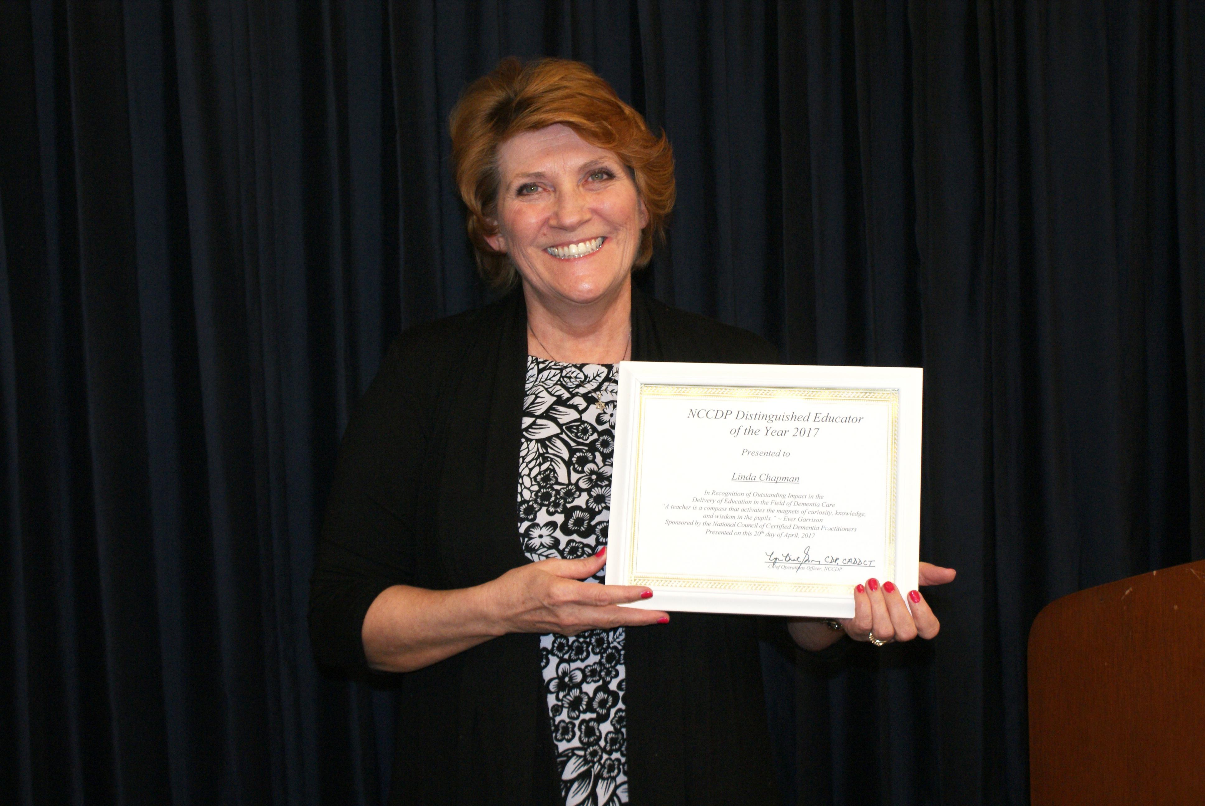 "Linda ""Andi"" Chapman holding her ""Educator of the Year"" award."