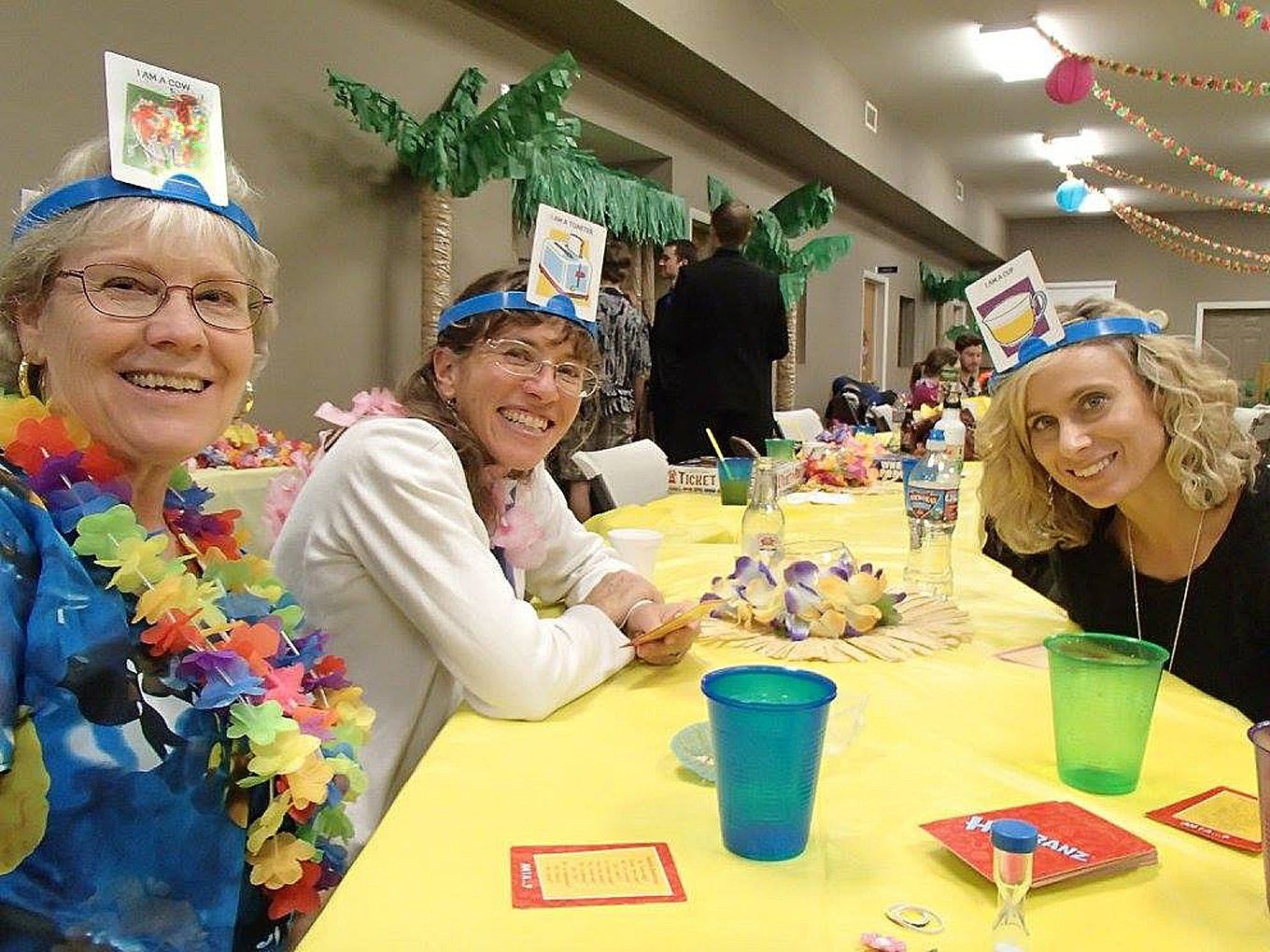 Left to right: Diane Oliver, Berenice Emehiser and Becky Oliver enjoy a game of Headbanz at the Luau.