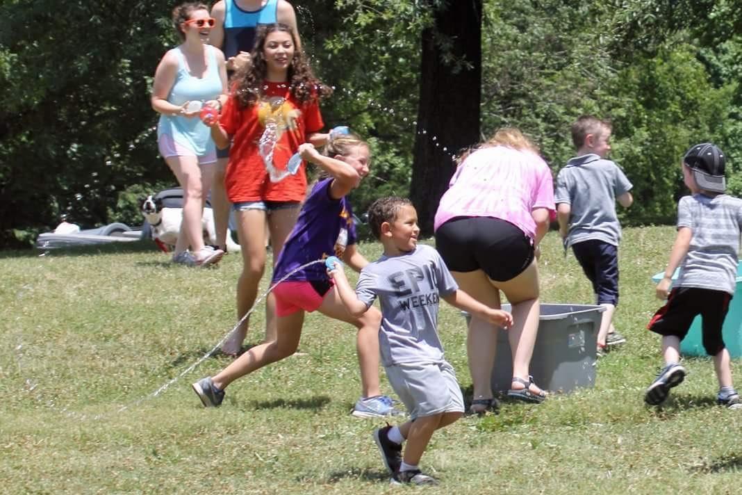 Members having a fun water balloon fight.