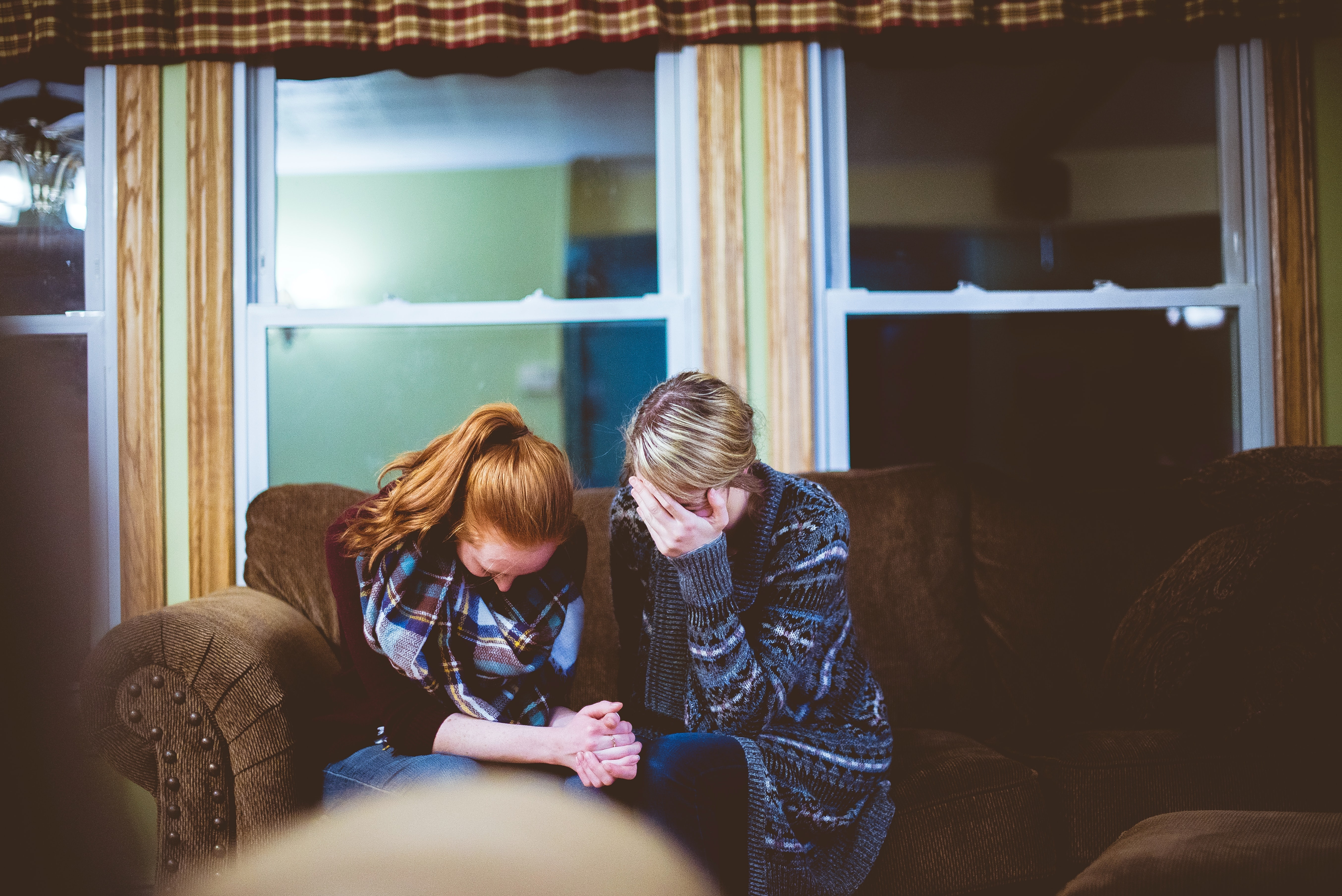 Photo of two women sitting on the couch grieving.