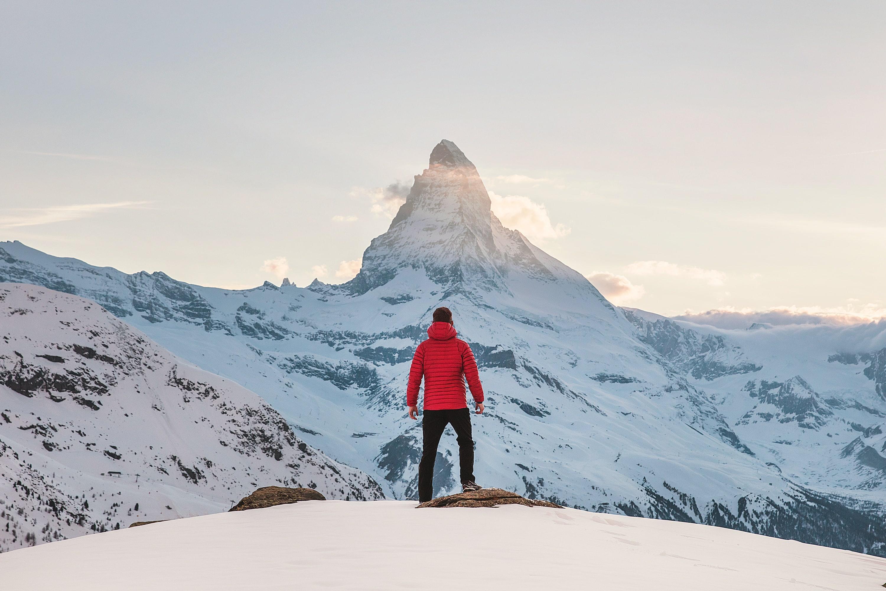 Photo of a man standing in front of a snowy mountain.