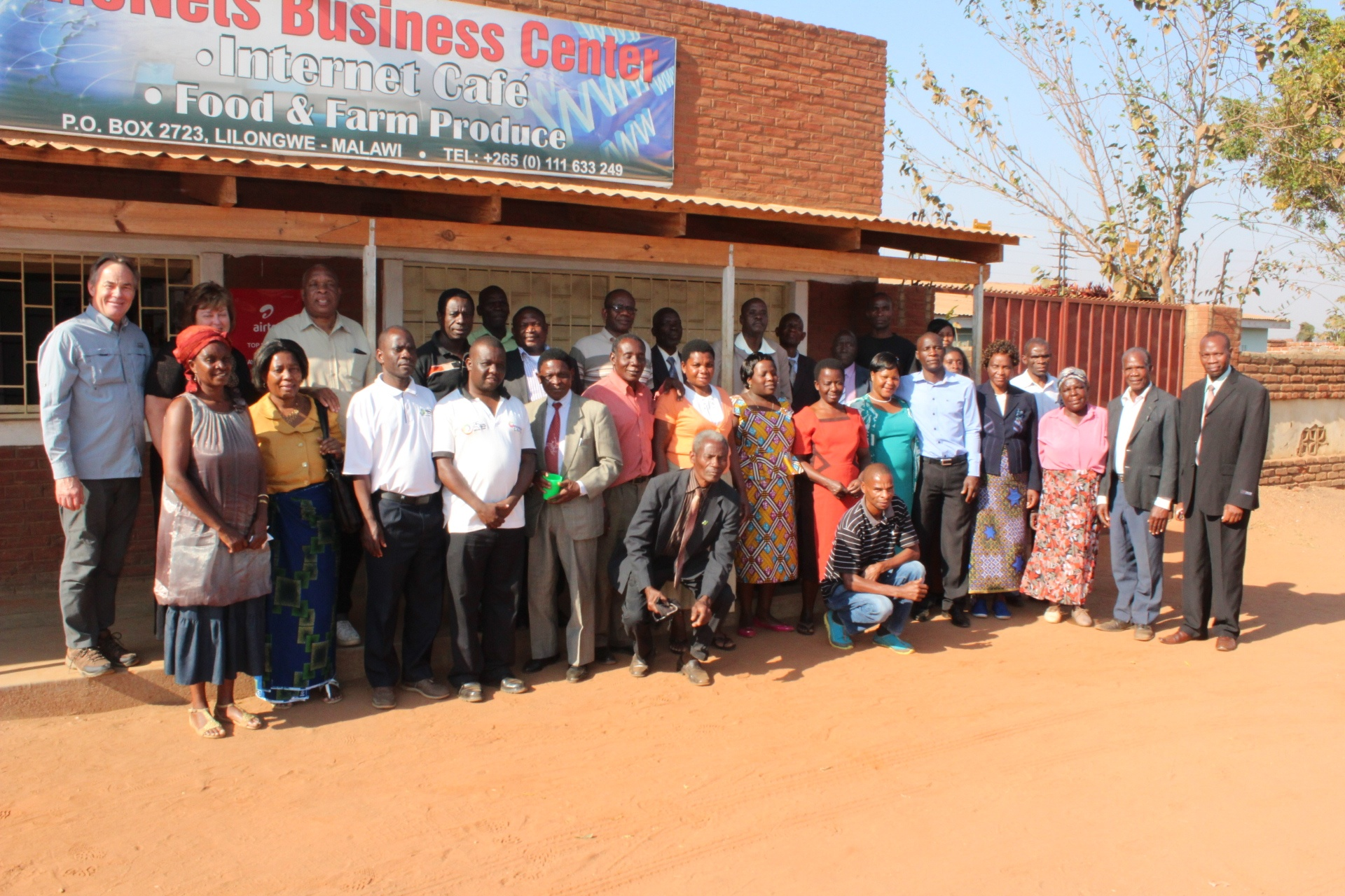 Darris and Debbie McNeely with brethren stand in front of the LifeNets Internet Cafe in Malawi.