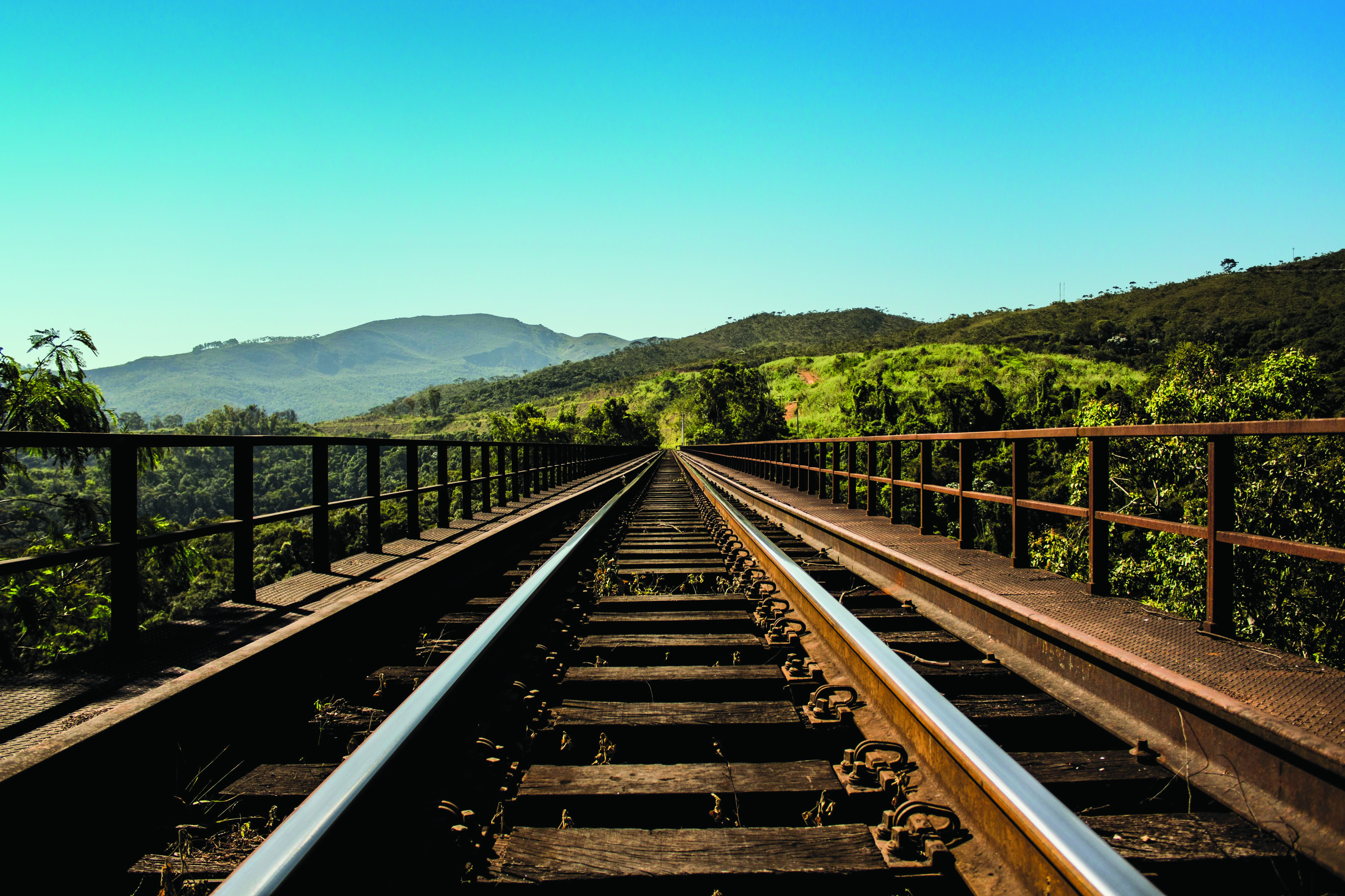 Photo of train tracks disappearing forward into the distant mountains.