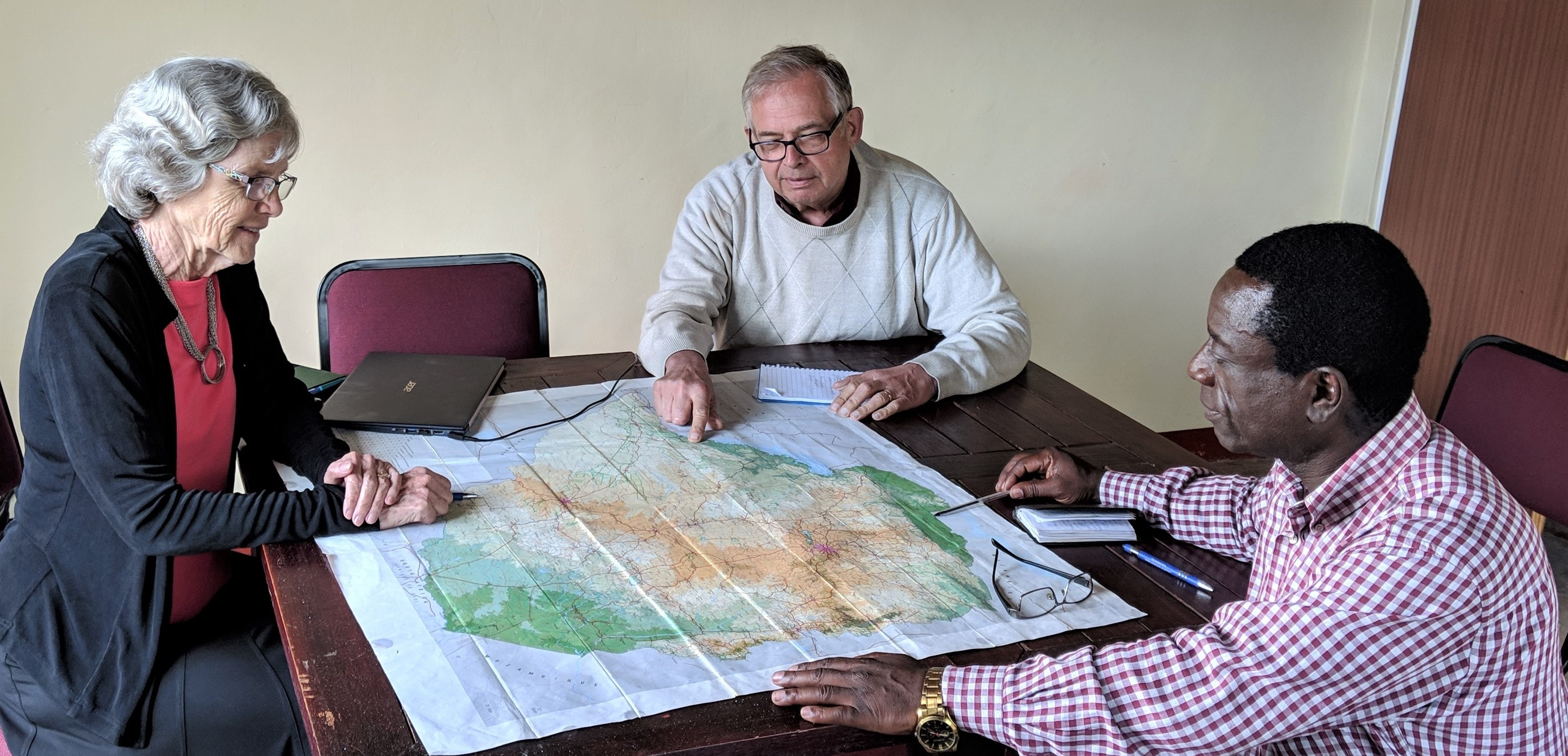 Mabasa Chichaya discusses the perils of Church members with Vic and Bev Kubik over a map of Zimbabwe.