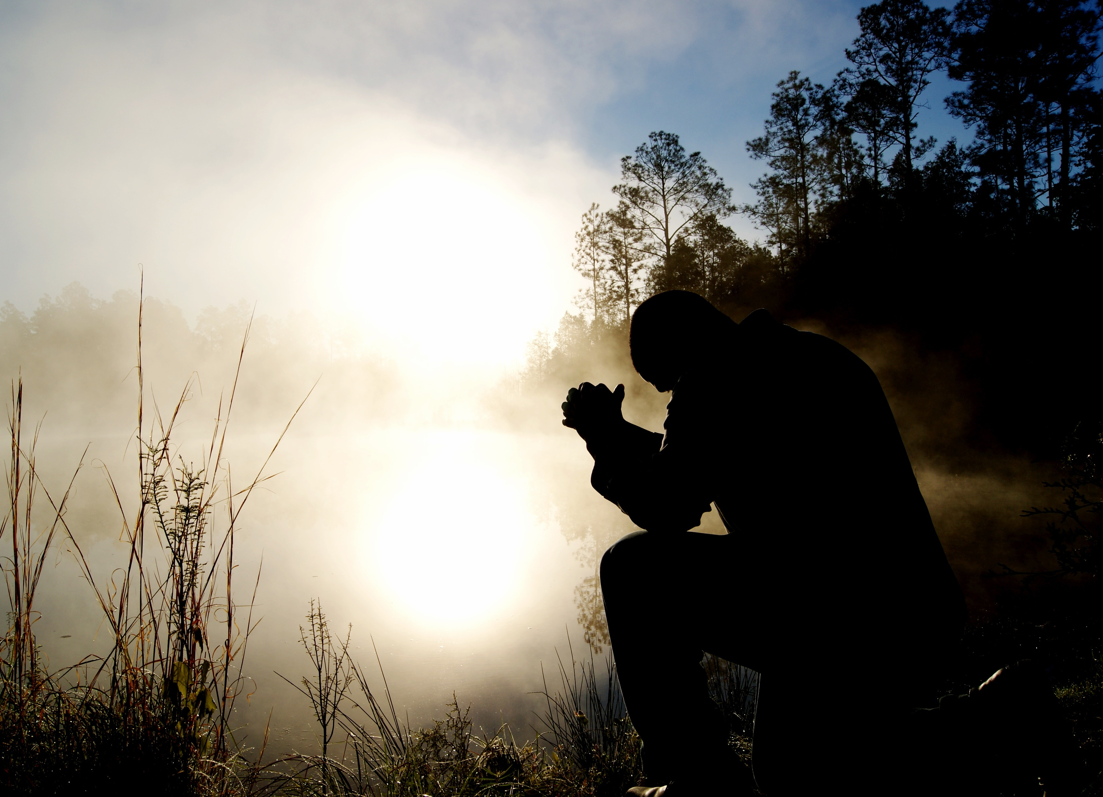 A man praying outside by a field lit by the morning sun.