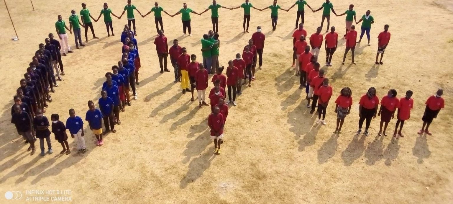 Photo of the youth at the camp in Zambia forming a UYC sign.
