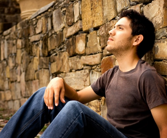 A young man sitting against a rock wall.