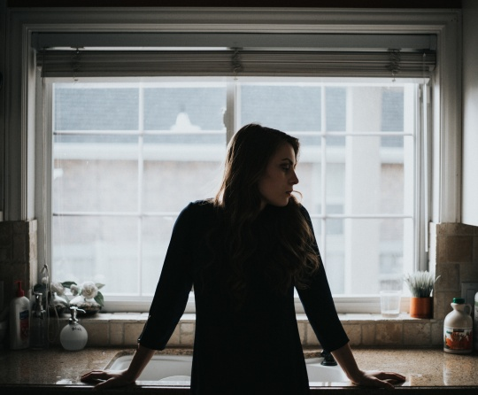 A woman standing by a kitchen sink.