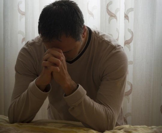 A man praying at the side of a bed.